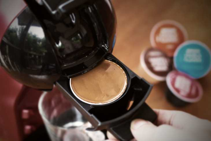 Hand putting pod into red coffee maker