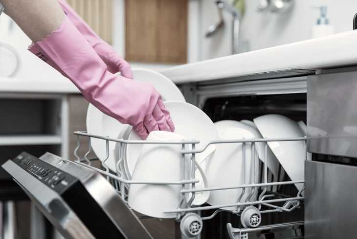Hands with pink gloves taking dishes out of dsihwasher