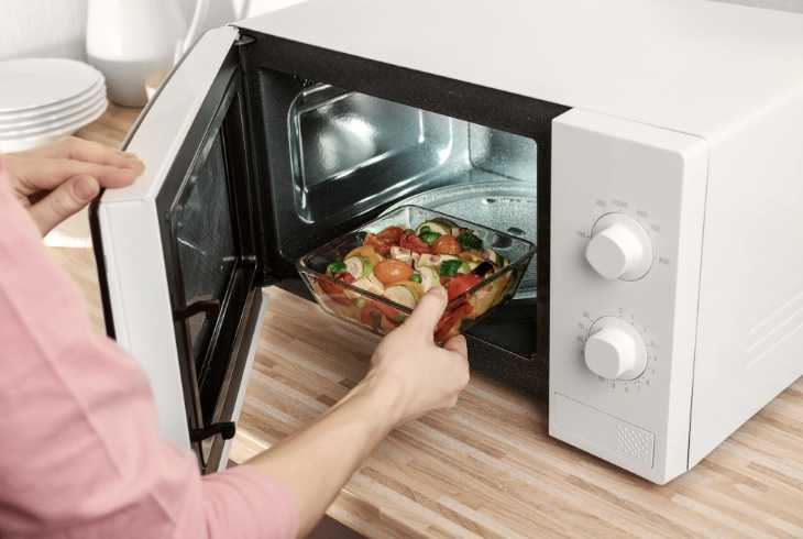 Arm putting food into the microwave oven