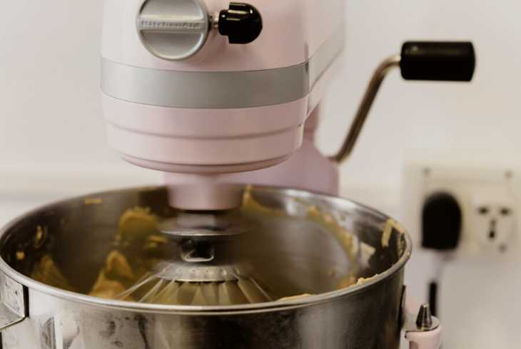 Pink stand mixer mixing ingredients